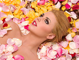 Flower Petals Spread out as Bedding for Beautiful Blond Woman