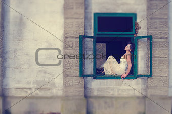 Beautiful girl standing on an open window in an old castle