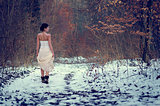 Lonely girl in white beautiful lace dress walking in a forest