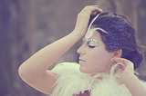 Beautiful girl fashion portrait with a feather bolero  Frozen bride make up  Eyes closed