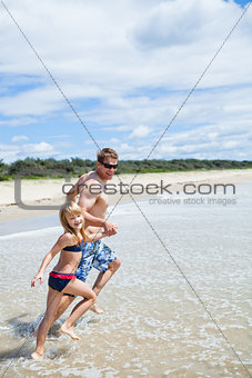 Happy father and daughter running along beach in shallow water