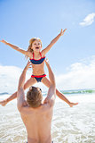 Father throwing young daughter in air at beach