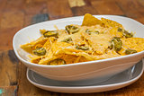 Nachos with cheese and jalapenos in a white bowl