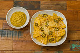 Nachos with cheese and jalapenos in a white bowl and fresh guaca