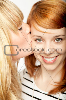 blond girl give red haired girl kiss