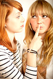 red haired and blond girl sign to shut up