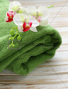 green towel and orchid flowers on a wooden background