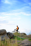 Cyclist with Bike in the Beautiful Mountains