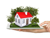 Hands holding tablet pc and small house with land