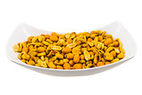 A bowl with salted and roasted peanuts and corn seeds