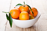 tangerines with leaves in bowl