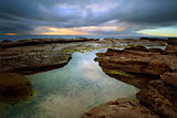 Stormy sunrise over Little Bay with rockpool in foreground