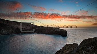Beautiful vibrant sunrise over rocky coastline
