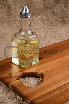 Olive oil in bottle on acacia wood board