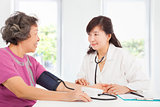 doctor measuring blood pressure of senior woman at home