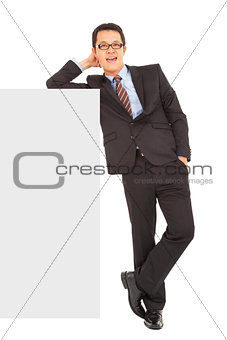 smiling businessman stand with blank wall