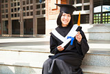 Asian college student holding a diploma at campus