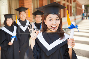 happy college graduate holding diploma  and make a gesture