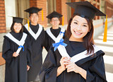 smiling college graduate holding diploma with classmates