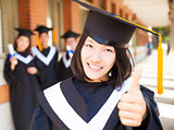 closeup pretty college graduate thumb up with classmates