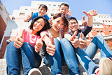 happy and smiling students thumbs up  together