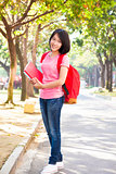 young student girl standing and holding books at campus