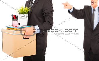An angry boss firing a man and carrying belongings
