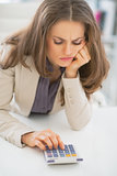 Frustrated business woman sitting in office and using calculator
