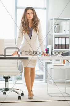 Thoughtful business woman standing in office