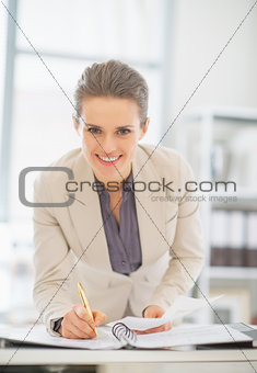 Portrait of smiling business woman working in office with docume