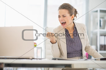 Happy business woman in office rejoicing success