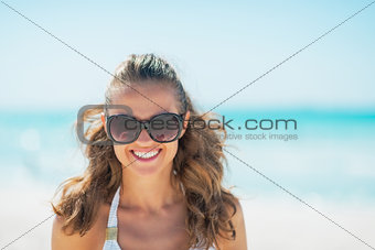 Portrait of young woman in sunglasses on beach