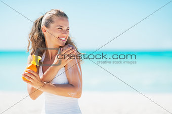 Young woman on beach applying sun block creme and looking on cop