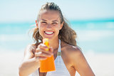 Smiling young woman pointing bottle of sun block creme in camera