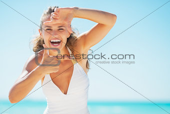 Smiling young woman on beach framing with hands