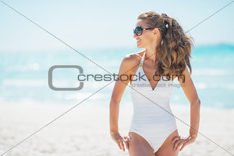 Young woman in sunglasses on beach looking on copy space