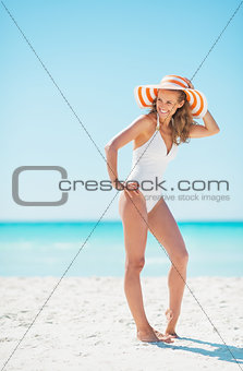 Full length portrait of young woman in hat standing on beach