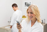 Smiling woman text messaging with man in background at kitchen