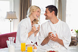 Happy couple looking at each other while having breakfast