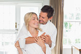 Loving man embracing woman from behind at home