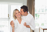 Loving young man kissing woman's cheek at home