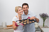 Portrait of couple with freshly baked cookies in kitchen