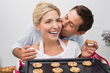 Man kissing woman's cheek as she holds freshly baked cookies in kitchen