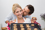 Man kissing woman's cheek as she holds freshly baked cookies