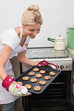 Smiling woman removing a tray of cookies from the oven
