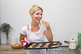 Smiling young woman with a tray of cookies in kitchen