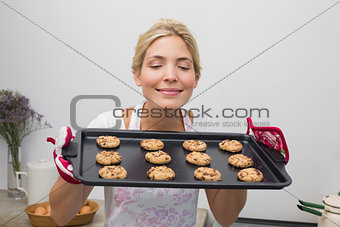 Woman holding a tray of cookies with eyes closed in kitchen
