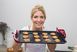 Smiling woman with a tray of cookies in the kitchen
