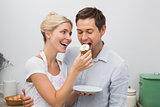 Happy woman feeding man pastry in kitchen