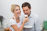 Happy young woman feeding man pastry at home